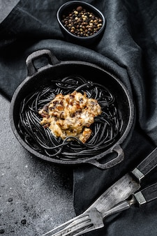 Macarrão espaguete preto com tinta de lula em uma panela. carne com molho de pimenta. fundo preto. vista do topo.