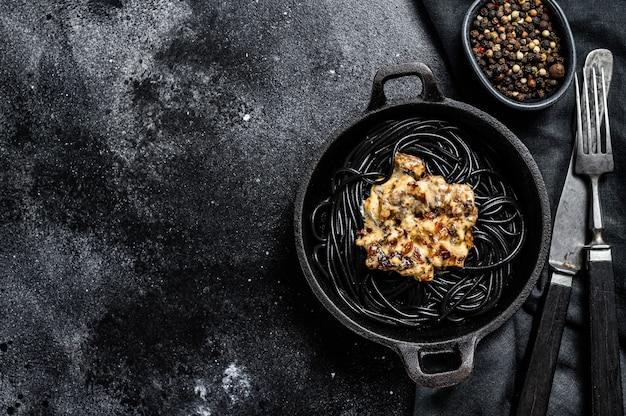 Macarrão espaguete preto com tinta de lula em uma panela. carne em molho de pimenta. fundo preto. vista do topo. copie o espaço