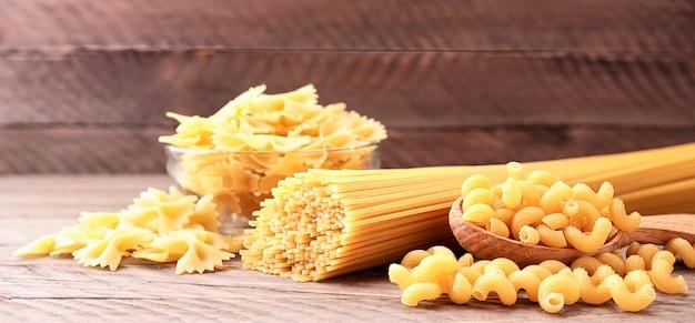 Macarrão espaguete sortido, borboletas, cachos em close-up de fundo de madeira