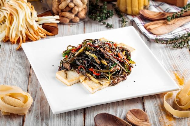 Macarrão estilo asiático com carne e queijo tofu em prato quadrado