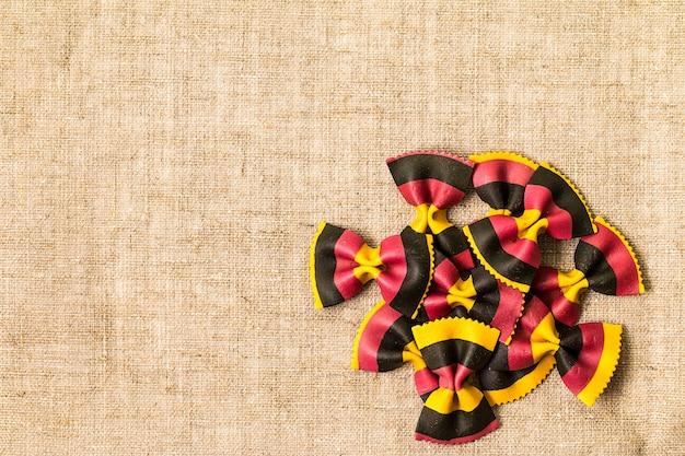Macarrão farfalle colorido cru conceito de culinária vista superior