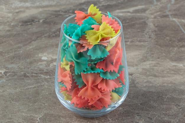 Macarrão farfalle colorido em vidro sobre superfície de mármore