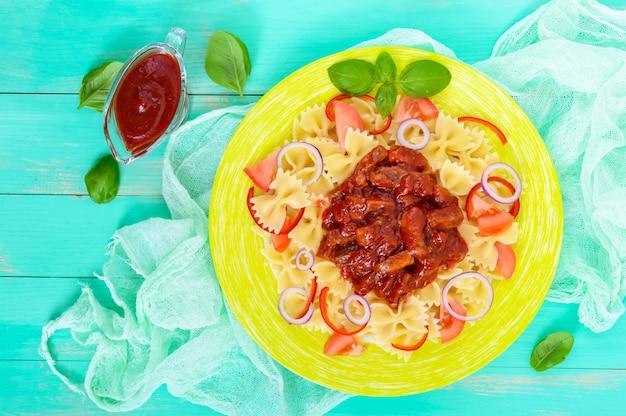 Macarrão farfalle com frango, tomate, cebola azul, pimentão e molho de tomate em um prato