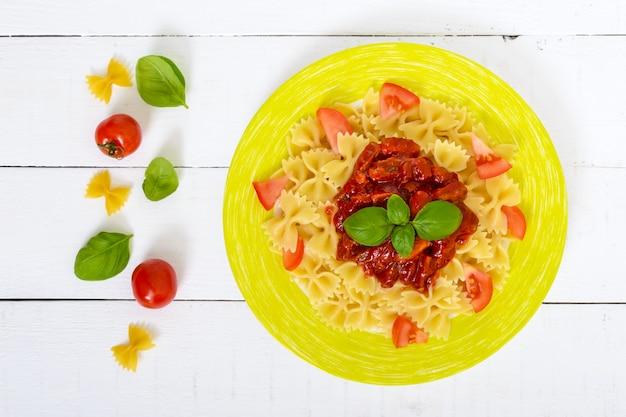Macarrão farfalle com frango, tomate e molho de tomate em um prato