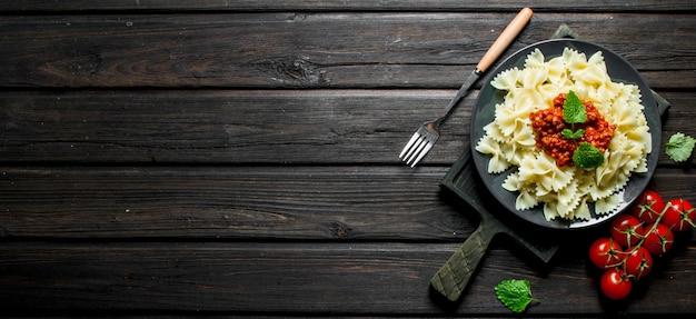 Macarrão farfalle com molho à bolonhesa no prato com tomate e folhas de hortelã. em fundo preto de madeira