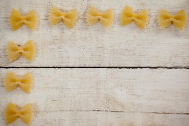 Macarrão farfalle disposto em uma fileira sobre fundo de madeira
