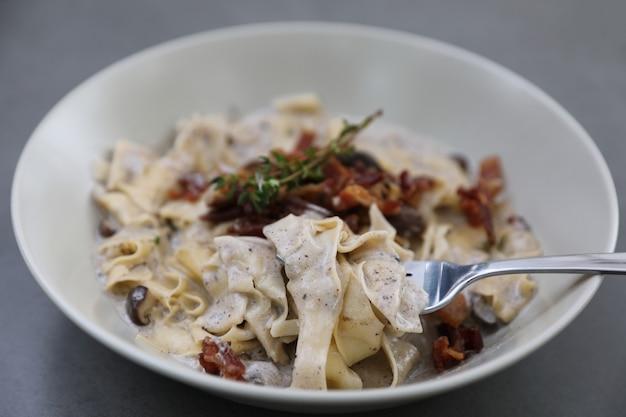 Macarrão fettuccine ao molho alfredo branco com presunto, bacon e cogumelos