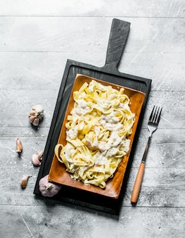 Macarrão fettuccine com molho carbonara e alho. em madeira
