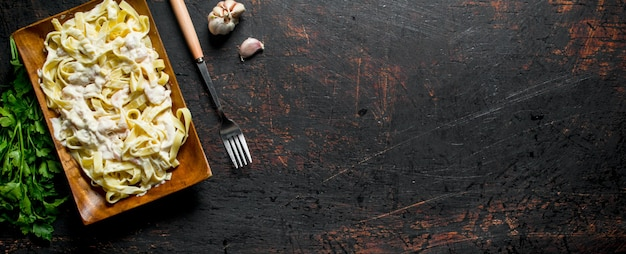 Macarrão fettuccine com molho carbonara no prato com alho e salsa. em rústico
