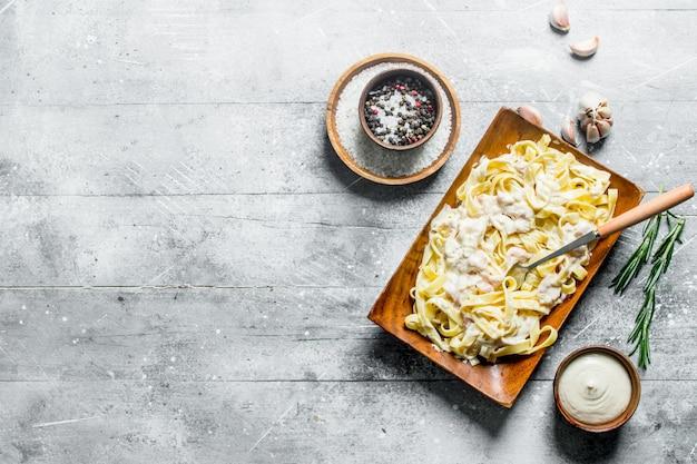 Macarrão fettuccine em um prato e molho em uma tigela. em fundo branco de madeira