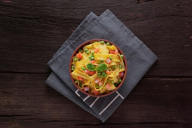Macarrão fettuccine em uma mesa de madeira em uma tigela. vista do topo. comida vegetariana.