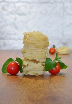 Macarrão fettuccine italiano sobre a mesa de madeira