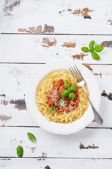 Macarrão fettuccine tradicional prato italiano com molho à bolonhesa, manjericão e queijo parmesão em um prato branco sobre uma superfície de madeira clara.