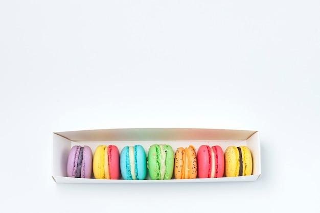 Macarrão francês doce e colorido em uma caixa branca sobre fundo branco