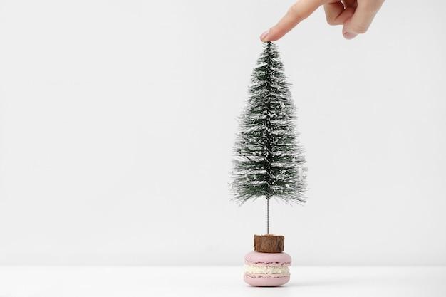 Macarrão francês ou sobremesa de macaroon na mesa branca. a mão da menina segura uma árvore de natal perto da sobremesa. preparando-se para as férias de natal.
