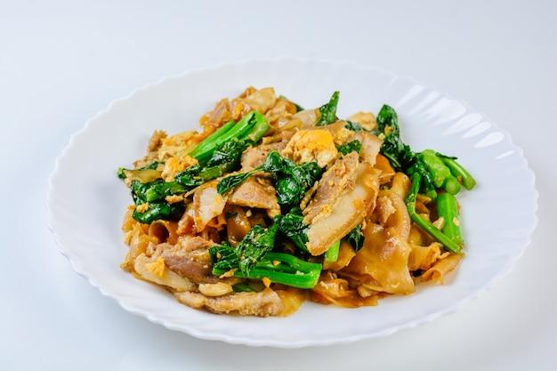 Macarrão fresco salteado da arroz-farinha com carne de porco, o ovo e a couve cortados. macarrão rápido salteado.