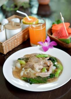 Macarrão frito com carne de porco embebido em molho, comida tailandesa