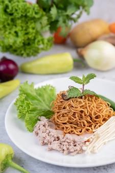 Macarrão frito com carne de porco picada, edamame, tomate e cogumelos em um prato branco.