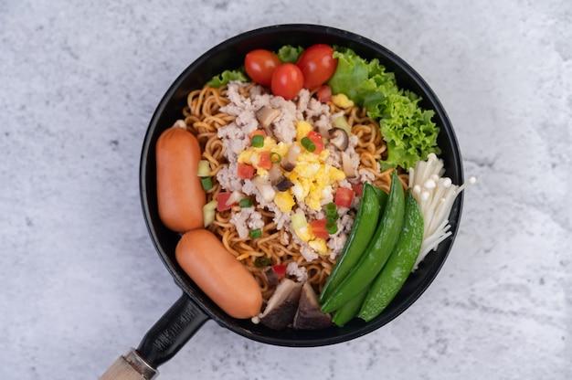 Macarrão frito com carne de porco picada, edamame, tomate e cogumelos em uma panela.