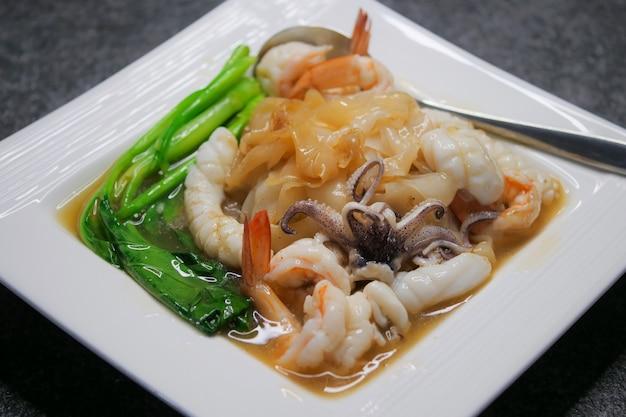 Macarrão frito com frutos do mar e couve no molho