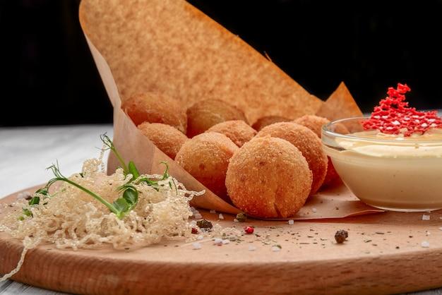Macarrão frito e queijo bolas servido com ketch up, foco seletivo