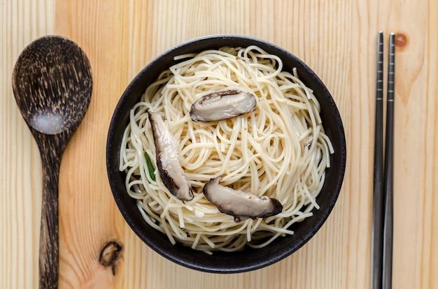 Macarrão frito em tigela preta na mesa de madeira, comida de rua tailandês