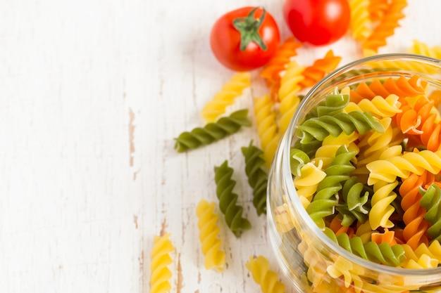 Macarrão fusilli colorido em uma jarra com tomates