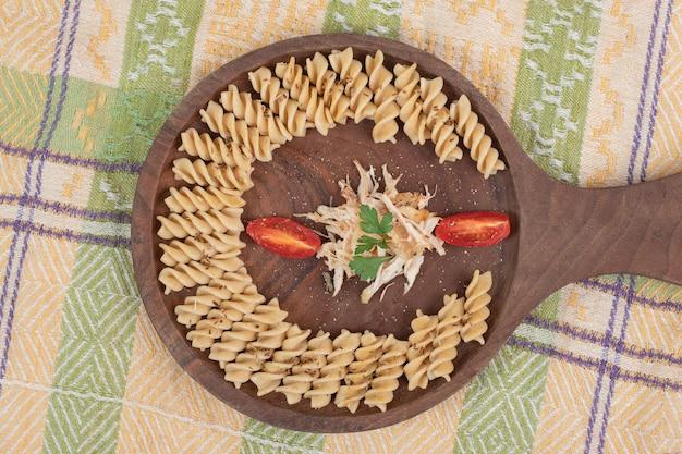 Macarrão fusilli e fatias de frango na placa de madeira.