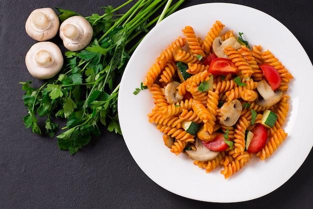 Macarrão fusilli italiano com abobrinha, tomate e cogumelos. comida vegetariana. em um prato branco, em um fundo cinza