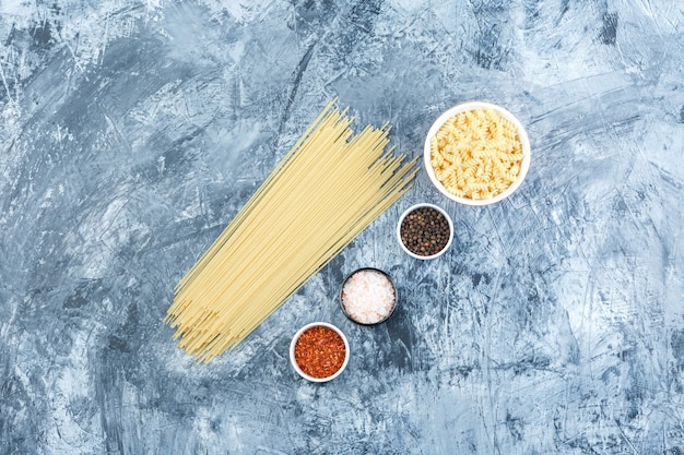 Macarrão fusilli plana leigos em uma tigela branca com espaguete, especiarias em fundo de gesso sujo. horizontal
