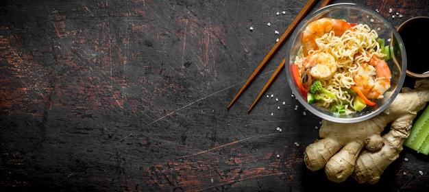 Macarrão instantâneo com legumes, camarão e gengibre fresco na mesa rústica.