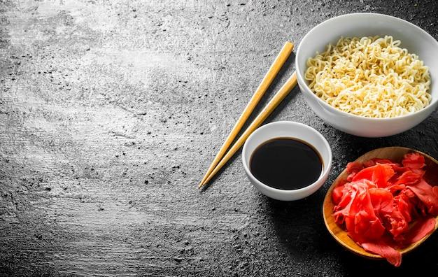 Macarrão instantâneo com molho de soja e gengibre na mesa rústica preta.
