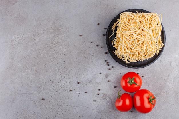 Macarrão instantâneo cru com tomates vermelhos frescos e grãos de pimenta.