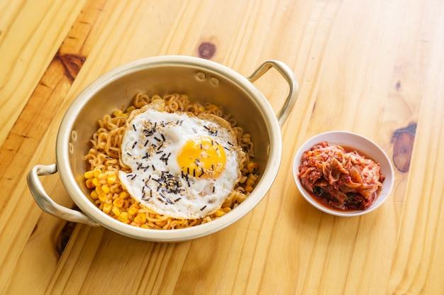 Macarrão instantâneo e kimchi do ovo em uma tabela de madeira.