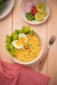 Macarrão instantâneo em uma tigela com legumes e ovo cozido no fundo de madeira