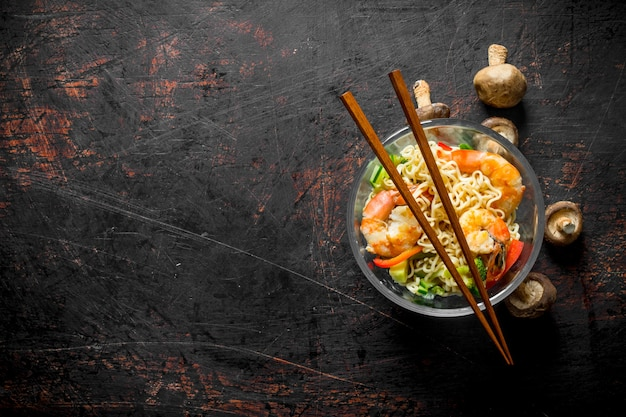 Macarrão instantâneo em uma tigela de vidro com camarão, legumes e cogumelos. em rústico escuro