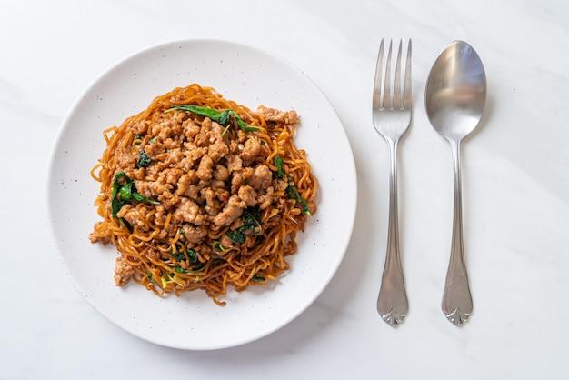 Macarrão instantâneo frito com manjericão tailandês e carne de porco picada - comida asiática