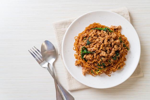 Macarrão instantâneo frito com manjericão tailandês e carne de porco picada
