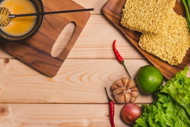 Macarrão instantâneo para cozinhar e comer no prato com ovo batido e legumes em fundo de madeira.
