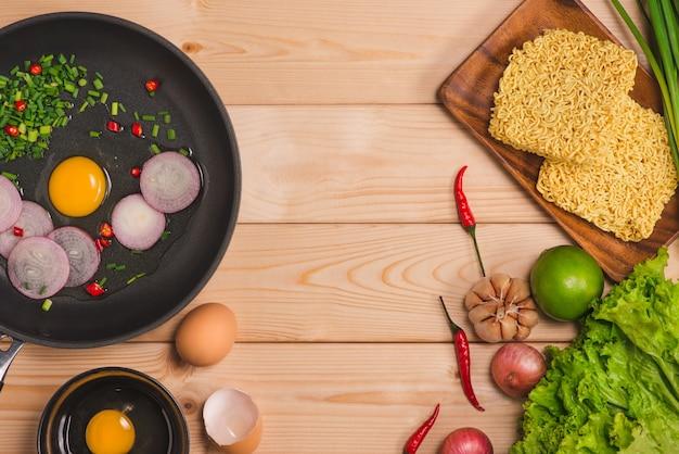 Macarrão instantâneo para cozinhar e comer no prato com ovos e legumes em fundo de madeira.