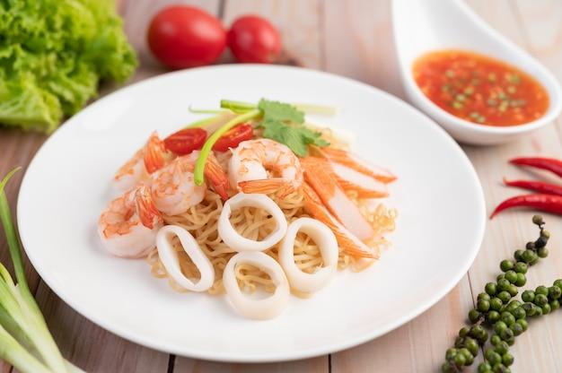 Macarrão instantâneo salteado com camarão e caranguejo em um prato branco.