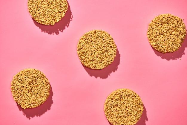 Macarrão instantâneo seco isolado em fundo rosa