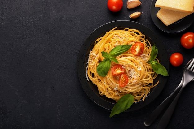 Macarrão italiano clássico apetitoso vegetal do espaguete do vegetariano com parmesão da manjericão, do tomate e do queijo na placa preta na tabela escura. ver os de cima, horizontal.