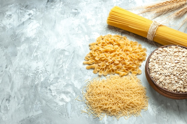 Macarrão italiano comprido de frente com massa pequena crua em formato diferente em cor de comida clara, muitos tipos de massa