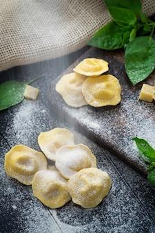 Macarrão italiano cru do ravioli com parmesão e manjericão em uma placa de madeira com farinha