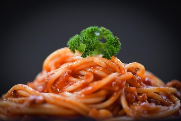 Macarrão italiano de espaguete close-up espaguete à bolonhesa em fundo preto