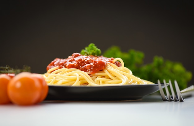 Macarrão italiano de espaguete servido na chapa preta com tomate e salsa no restaurante comida italiana e conceito de menu - espaguete à bolonhesa