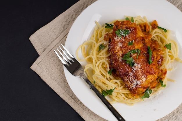 Macarrão italiano de frango à parmegiana com ervas e molho de tomate. sobre um fundo cinza. vista do topo.