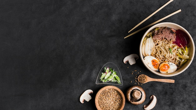 Macarrão japonês caseiro de porco com ovos e ingredientes em pano de fundo preto