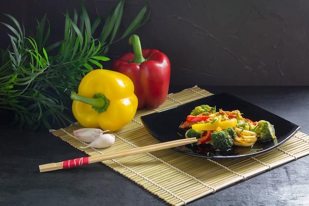 Macarrão japonês frite com legumes em um prato preto com molho de soja e ingredientes em uma esteira de bambu